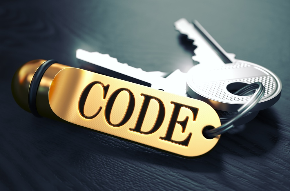 Keys and Golden Keyring with the Word Code over Black Wooden Table with Blur Effect. Toned Image..jpeg